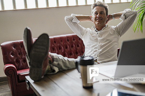 Smiling businessman sitting with feet on desk