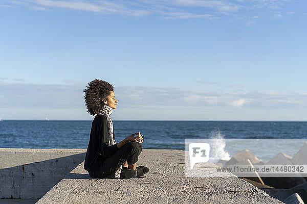 Frau sitzt auf Mauer vor dem Meer und meditiert
