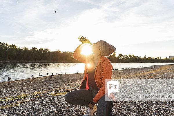 Sportliche Frau macht Pause am Fluss  Trinkwasser