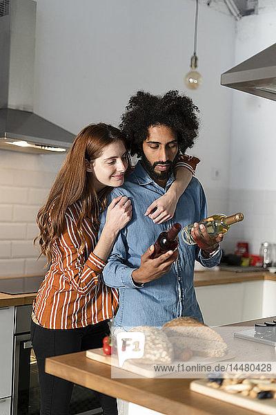 Ehepaar steht in der Küche  bereitet das Abendessen vor  wählt den Wein