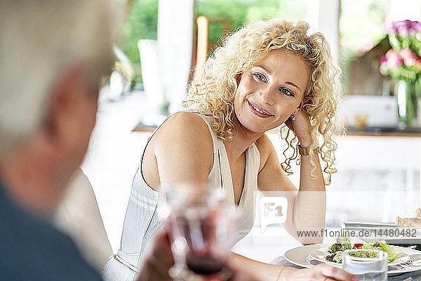 Lächelnde junge Frau beim Essen mit der Familie