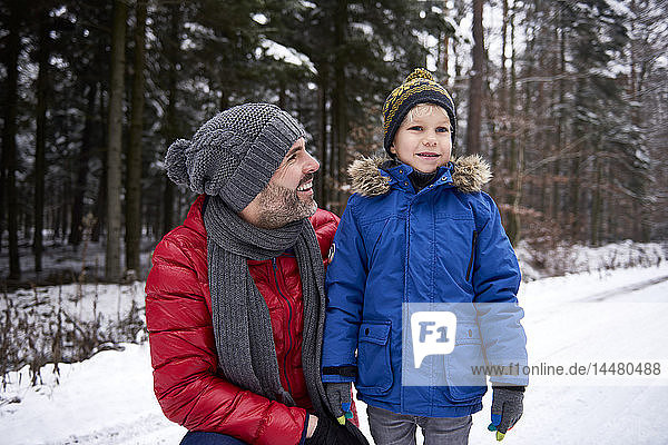 Father and son together in winter forest