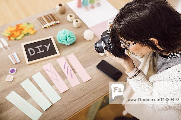 Junge Frau fotografiert mit einer Kamera für ihren Bastel-Blog