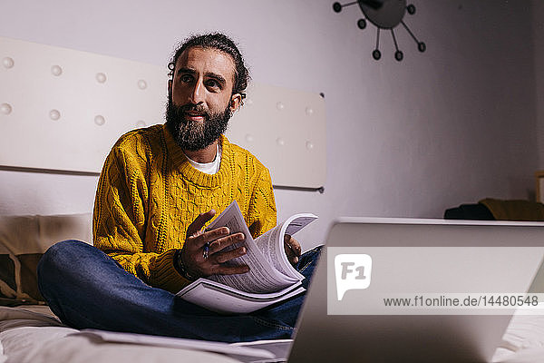 Young man working in bed at home with laptop and documents