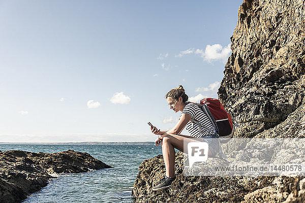 Junge Frau sitzt an einem felsigen Strand und benutzt ein Smartphone