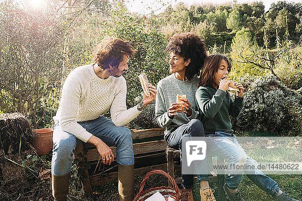 Glückliche Familie im Garten sitzen,  eine Pause machen,  Sandwiches essen