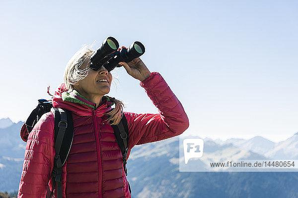 Österreich  Tirol  Frau  die während einer Wanderung durch ein Fernglas schaut