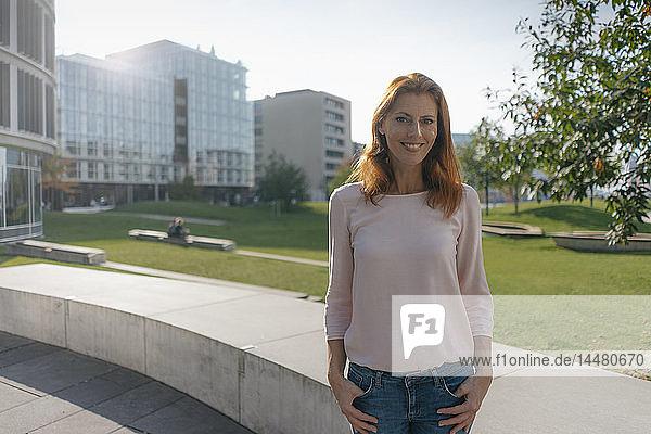 Porträt einer lächelnden Geschäftsfrau im Freien in der Stadt