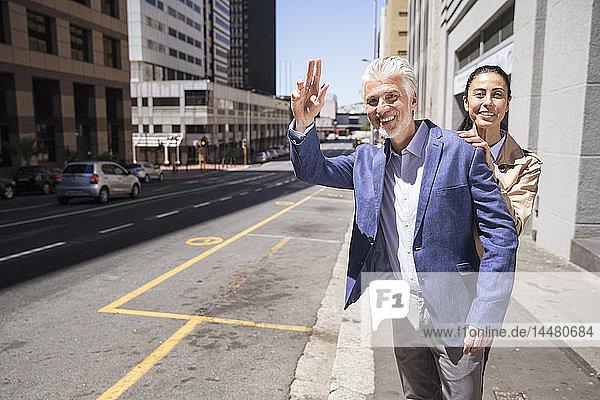 Ein reifes Paar in der Stadt  das ein Taxi ruft