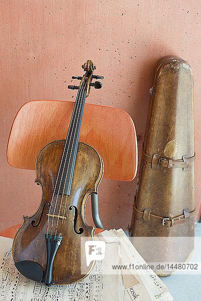 Geige und Noten auf Holzstuhl mit Geigenkasten im Hintergrund