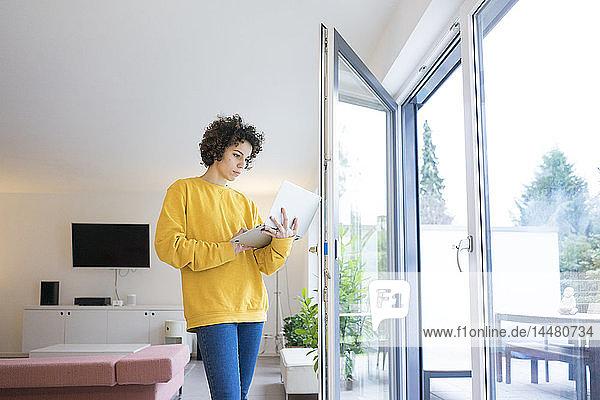 Frau mit Laptop am Fenster zu Hause