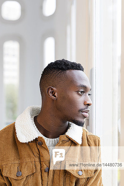 Young man with shaved head and beard looking out of window