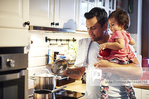Father preparing meal and holding baby girl in kitchen at home