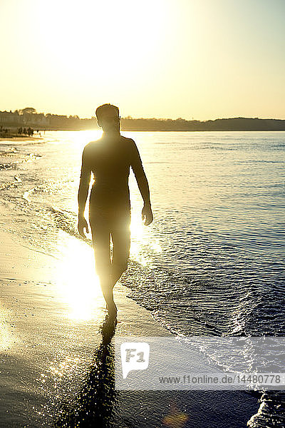 Silhouette of man  walking at the beach at sunset