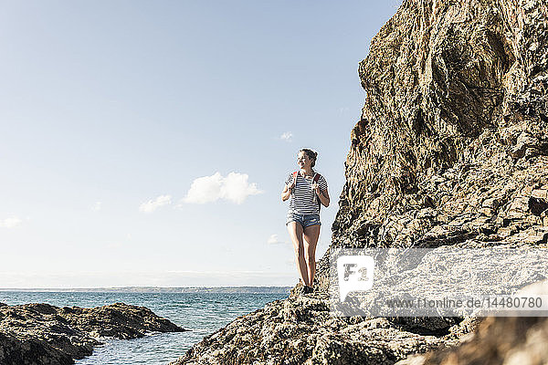 Young woman hiking on a rocky beach  looking at view