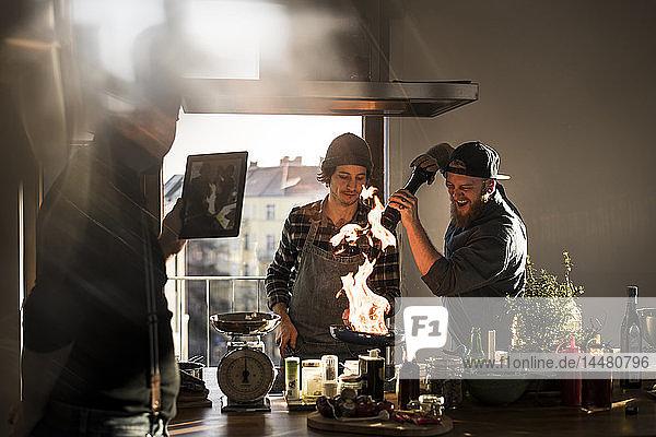 Freunde flambieren Lebensmittel in einer Pfanne und erzeugen eine große Flamme  während der Freund filmt
