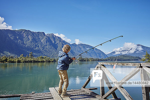 Chile  Chaiten  Lago Rosselot  boy standing on jetty fishing in lake