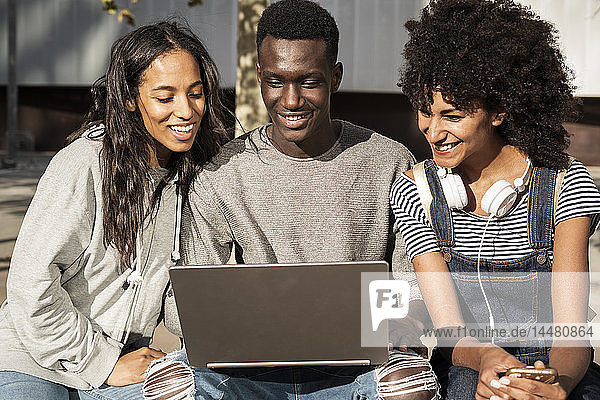 Friends sitting on a bench in the city  having fun  using laptop