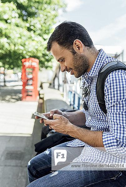 Großbritannien  London  lächelnder Mann benutzt sein Smartphone auf der Straße