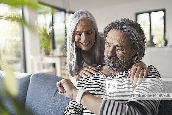 Älteres Ehepaar schaut auf Smartwatch