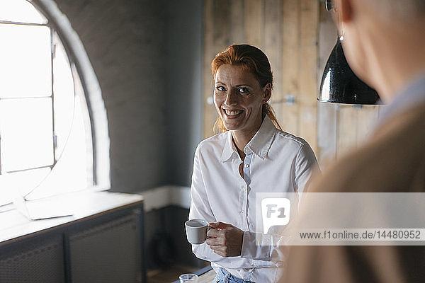 Lächelnde Geschäftsfrau mit einer Tasse Kaffee im Büro  die einen älteren Mann ansieht