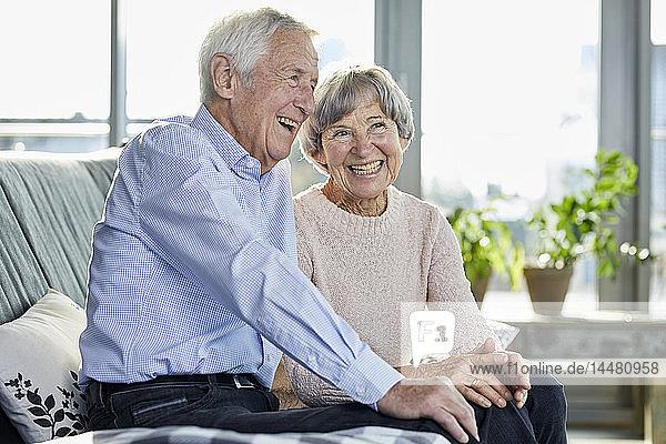Porträt eines lachenden Seniorenpaares  das zusammen auf der Couch sitzt