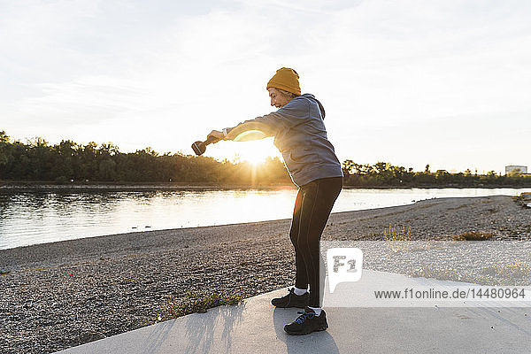 Senior woman exercising with a kettlebell at the river
