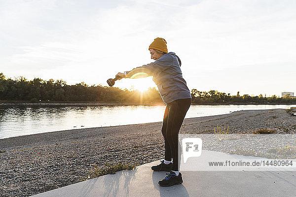 Ältere Frau übt mit einer Kesselglocke am Fluss