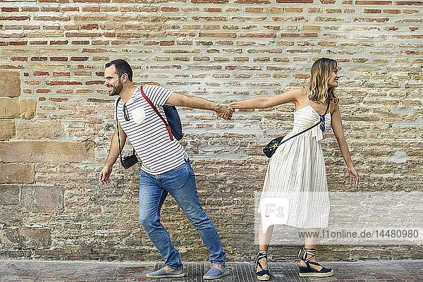 Paar hält sich an der Ziegelmauer an den Händen und geht in entgegengesetzte Richtungen