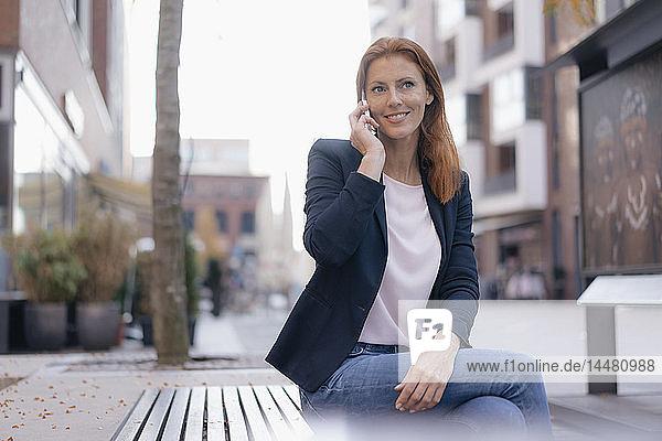Lächelnde Geschäftsfrau am Mobiltelefon  die draußen in der Stadt sitzt