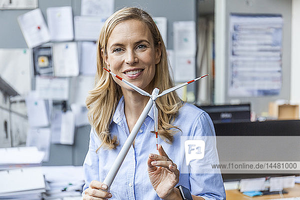 Porträt einer lächelnden Frau im Büro mit einem Modell einer Windkraftanlage