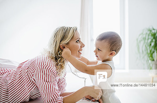 Smiling mother and toddler son using earphones in bedroom at home