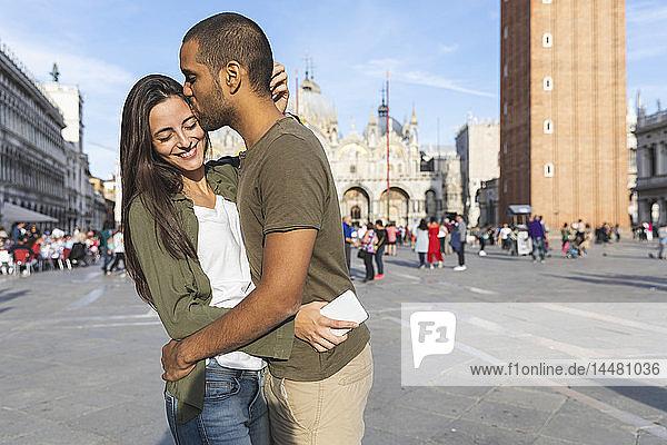 Italien  Venedig  glückliches Touristenpaar küsst sich auf dem Markusplatz
