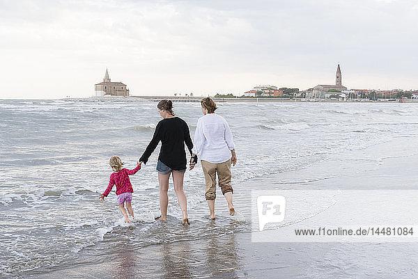 Italien  Caorle  zwei Frauen gehen mit einem Mädchen am Wasser