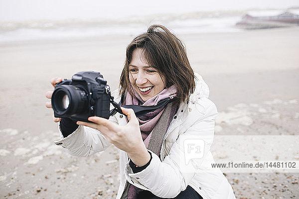 Porträt einer entspannten Frau,  die am Strand mit der Kamera fotografiert