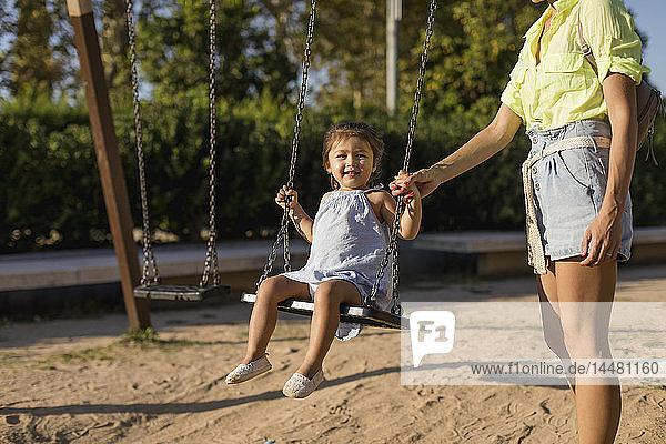 Mutter hält die Hand ihrer Tochter auf einem Spielplatz schwingend