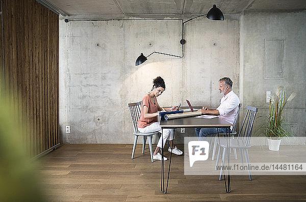 Geschäftsmann und Geschäftsfrau arbeiten am Tisch in einem Loft