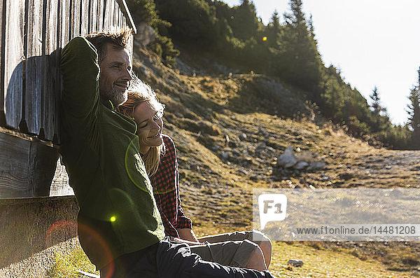 Wanderndes Ehepaar sitzt vor der Berghütte und macht eine Pause