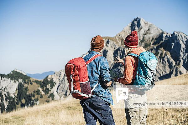 Österreich  Tirol  Paar mit Karte Wandern in den Bergen