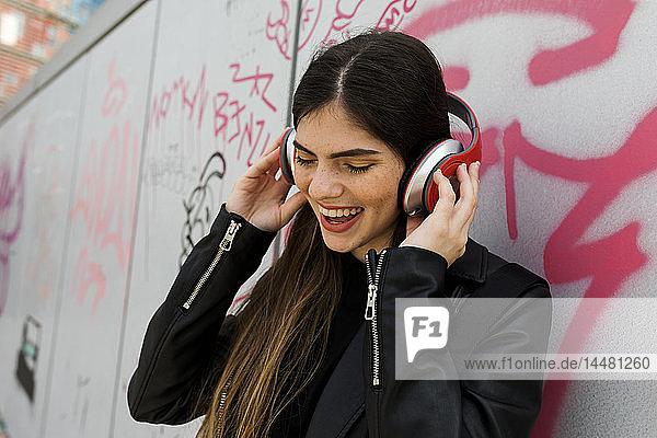 Glückliche junge Frau hört Musik mit Kopfhörern an Graffiti-Wand