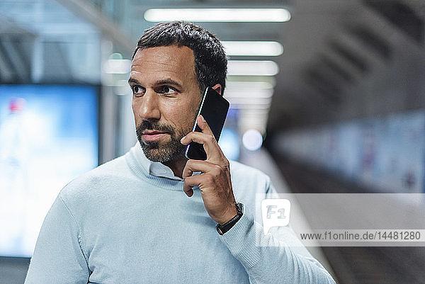Geschäftsmann benutzt Smartphone an der U-Bahn-Station