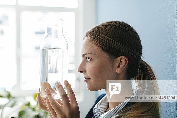 Junge Geschäftsfrau hält Karaffe mit frischem Wasser