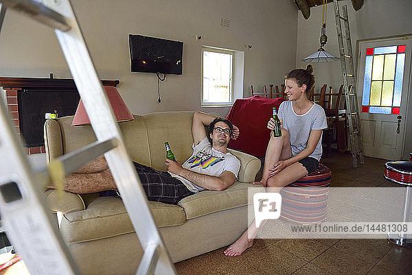 Glückliches junges Paar  das eine Pause von der Renovierung seines Hauses einlegt