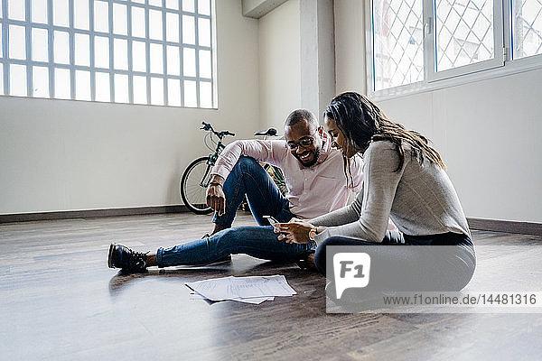 Lächelnder Geschäftsmann und Geschäftsfrau sitzen auf dem Boden mit Handy und Dokumenten