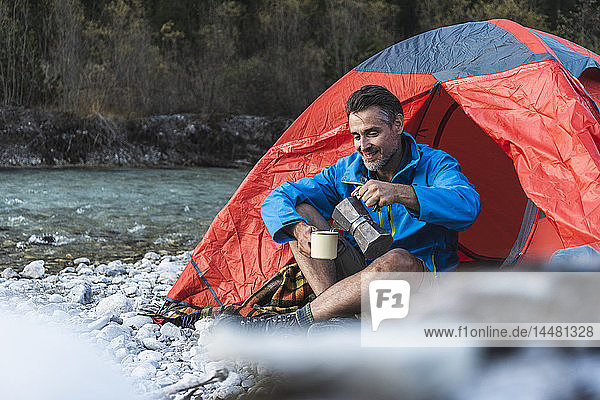 Erwachsener Mann zeltet am Flussufer  Espressomaschine und Tasse