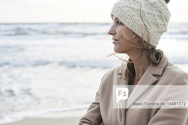 Spain  Menorca  profile of senior woman wearing wooly hat on the beach in winter