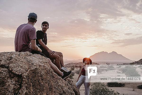 Namibia  Spitzkoppe  Freunde sitzen bei Sonnenuntergang auf einem Felsen