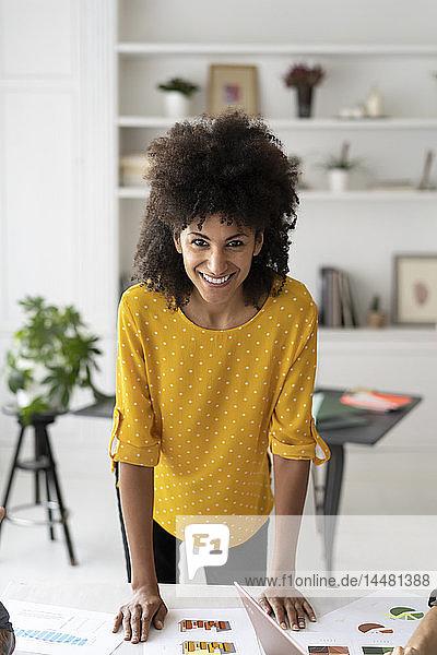 glückliche Geschäftsfrau  die sich auf den Schreibtisch lehnt und lächelt