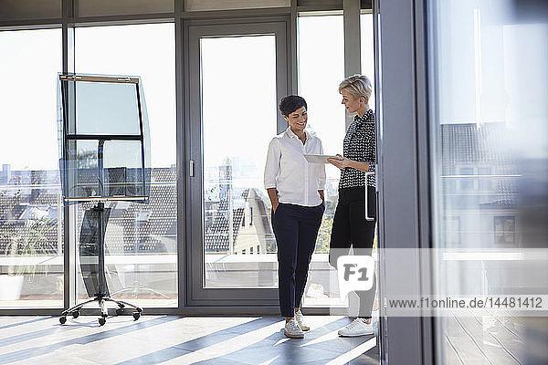 Zwei lächelnde Geschäftsfrauen betrachten Tablette am Fenster in einem hellen Büro