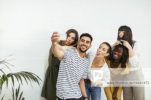Playful colleagues standing at brick wall taking a selfie
